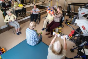 Caregiver with a group of seniors lifting weights