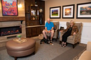 Senior couple in chairs with dog at their feet